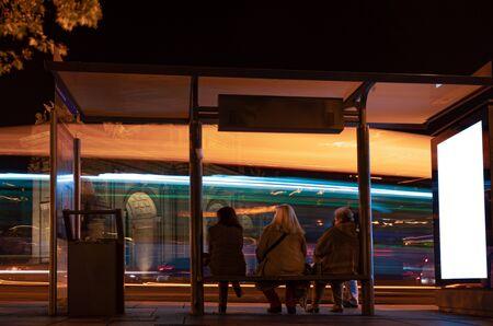 Groupe de personnes anonymes attendant les transports publics dans une gare routière de nuit avec panneau d'affichage. Écran blanc vierge Banque d'images