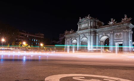 Night view of Puerta de Alcala with traffic lights in Madrid, Spain.