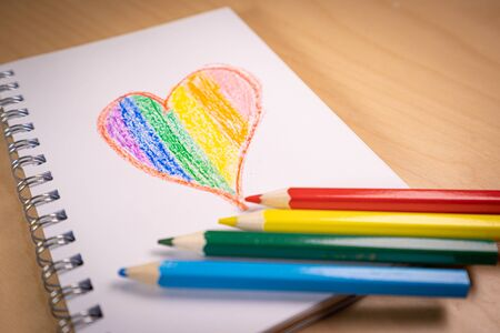Heart with the colors of the LGTBI or GLBT flag on a blank notebook with rainbow pens