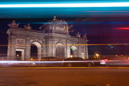 Night view of Puerta de Alcala with traffic lights in Madrid, Spain. Copy space available and 30 km per hour urban limit sign.