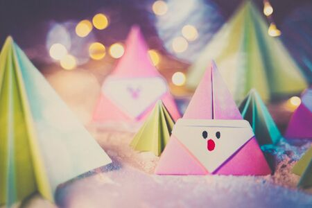 Origami Xmas scene with a pink Santa claus and crhistmas trees in paper craft