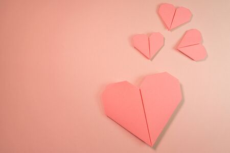 Pink origami hearts on a pink background Stock fotó