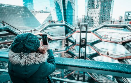 Beautiful curly brunette woman taking a photo in The Vessel at the Hudson Yards Stock Photo
