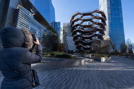 Woman with warm winter clothes taking a photo with her smartphone in Hudson Yards. Stock Photo
