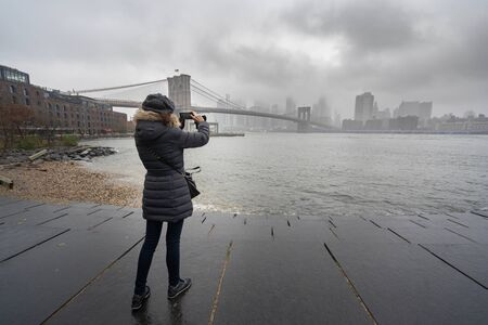 Tourist woman with warm clothes taking a picture of Brooklyn Bridge 版權商用圖片