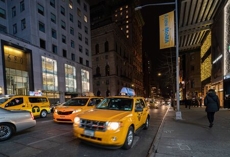 Yellow Taxis in New York City on 5th Ave by night