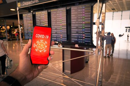 Hand holding a smartphone with Covid-19 message on screen and airport timetables as background. Archivio Fotografico