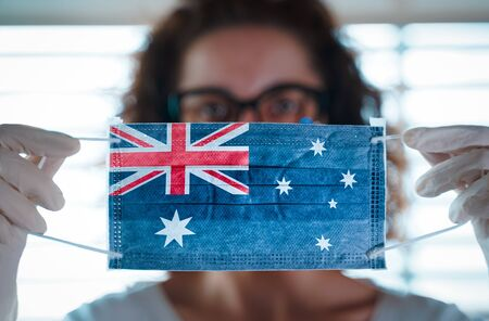 Pandemic Coronavirus. Close up of young woman with surgical mask with the flag of Australia on it