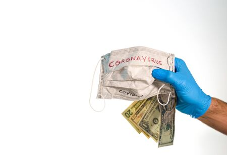 Hand with dollar bills and a face mask with the word coronavirus isolated on white