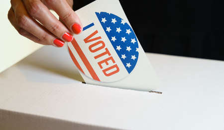 USA elections, Woman voter putting a vote in a ballot box