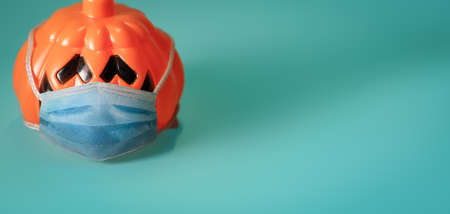 Orange pumpkin wearing a protective medical mask. Archivio Fotografico