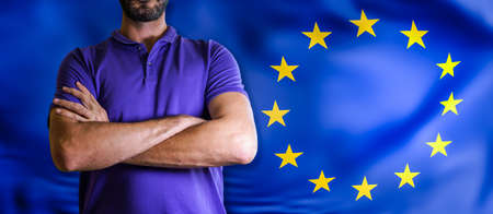 Torso of a man Young man with arms crossed against EU flag