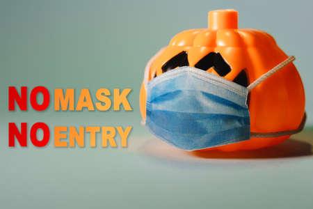 Orange pumpkin wearing a protective medical mask.