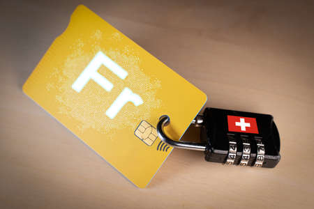 Padlock closed around a credit card with digital Swiss franc on it Banco de Imagens