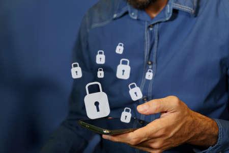 Man using a smartphone with padlock icons. Standard-Bild