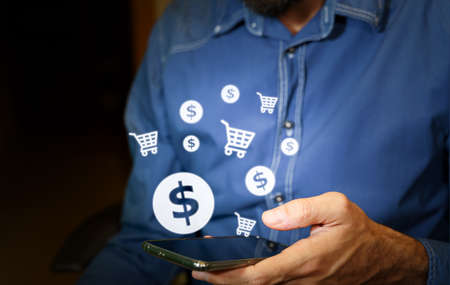Man using a smartphone with US dollar and shopping cart icons. Standard-Bild