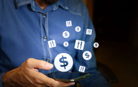 Man using a smartphone with US dollar and food or restaurant icons. Standard-Bild