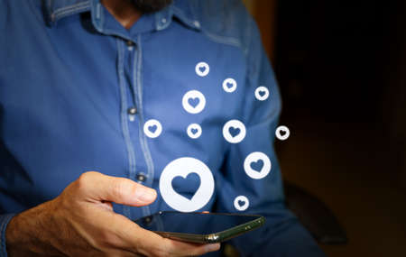 Man using a smartphone with heart icons.