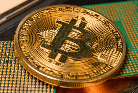 Golden coin with bitcoin symbol on a mainboard