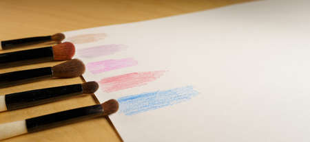 makeup brushes in a row on a paper with color swatches