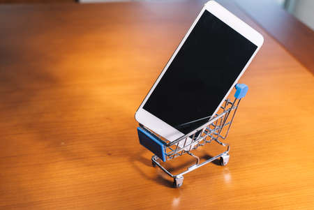 Smartphone inside a small shopping cart, online shopping concept