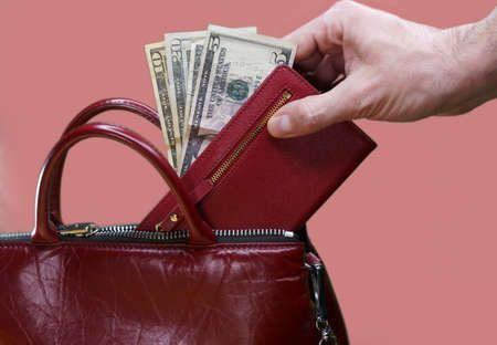 Hand stealing wallet with money from inside a purse 版權商用圖片