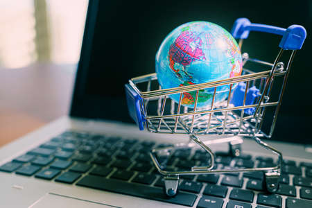 Small shopping cart with world globe in it over a laptop.