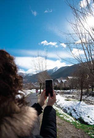 Beautiful curly brunette woman taking selfie self-portrait on snow mountain