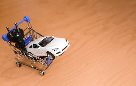 Toy car and electrical plug inside a small shopping cart