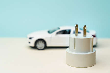 Toy car and electrical plug. Electric car and green car concept