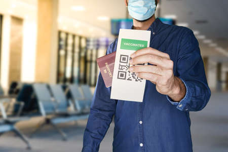 A man wearing a face mask and holding a passport and a Green pass certificate of vaccination.