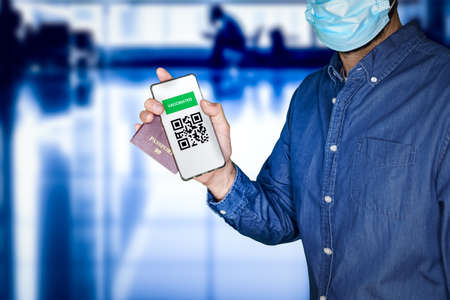 unidentified man wearing a face mask and holding a passport and a Green pass meaningless QR code representing a certificate of vaccination.