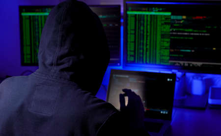 man in a hood working as a hacker at the computer in the dark room at night, hacking the system and laundring secret information.