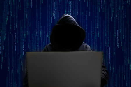 silhouette of a man in a hood working as a hacker at the computer in the dark room at night, hacking the system and laundring secret information. 版權商用圖片