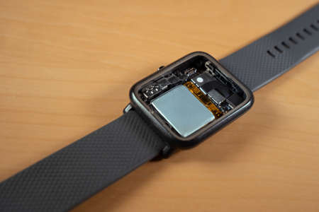 Disassembled smartwatch showing the interior, battery, different sensors and CPU.