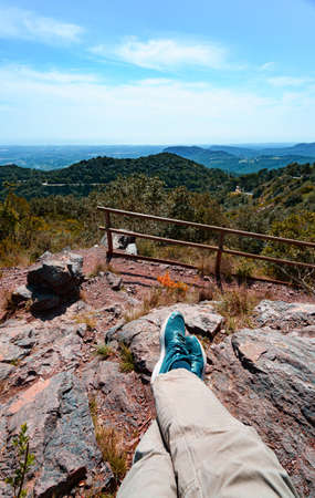 First person perspective shot from a hiker sitting Hiker sitting on top of a mountain at Argentera Ridge, catalonia, Spain