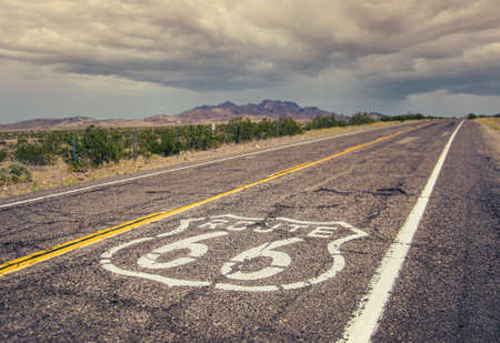 Long US road with a Route 66 sign painted on it 版權商用圖片