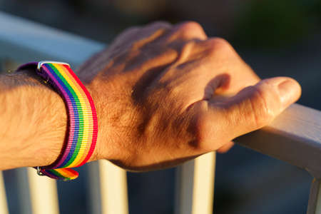 close-up view of a mans hand with an LGBT rainbow wristband.
