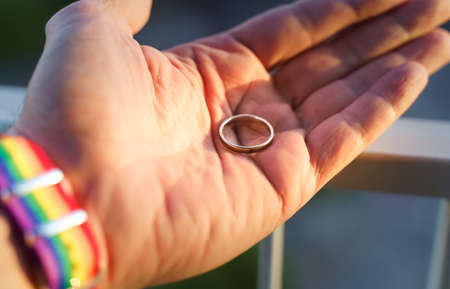 close-up view of a mans hand showing a ring with an LGBT rainbow wristband.