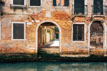 A brick building over a small narrow canal in Italy, Venice