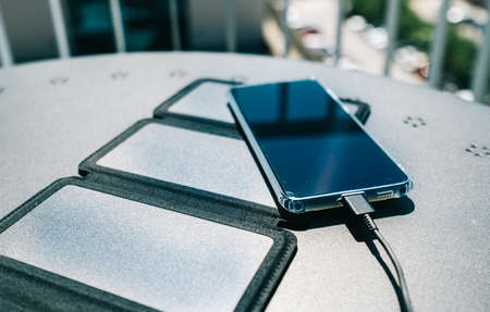 Charging a smartphone from home with a portable solar panel charger.Self-consumption and charging with small solar panels i