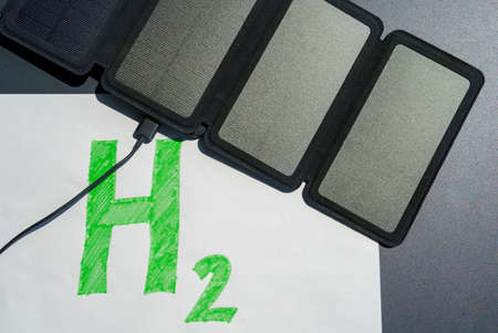 Green hydrogen concept. Solar panel connected to H2 text, symbolizing the generation of hydrogen from solar energy without fossil fuels.