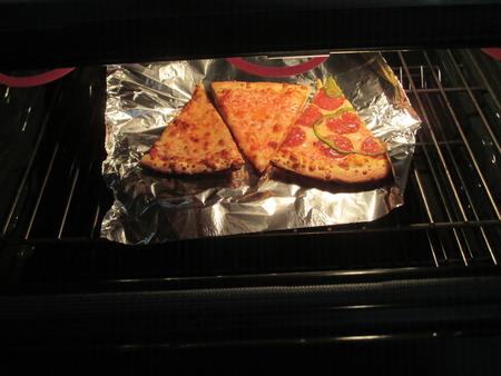 foil: Pizza warming up in an oven Stock Photo