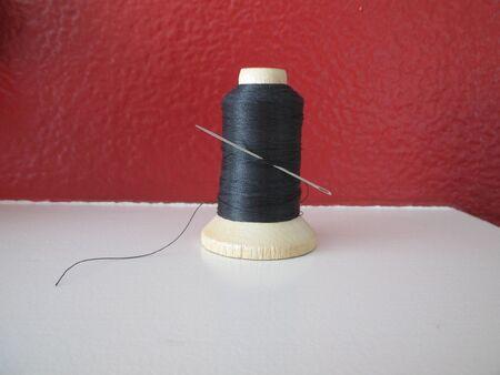 tread: A spool of black thread