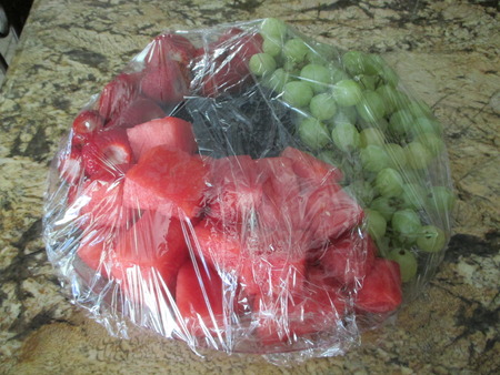 A plastic wrapped fruit platter