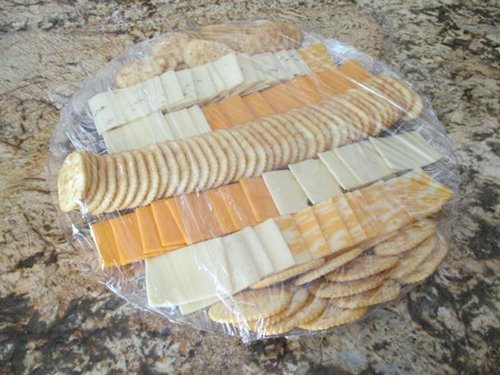 A plastic wrapped cheese and cracker platter