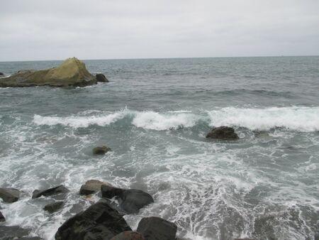 olas de mar: Ocean waves over rocks