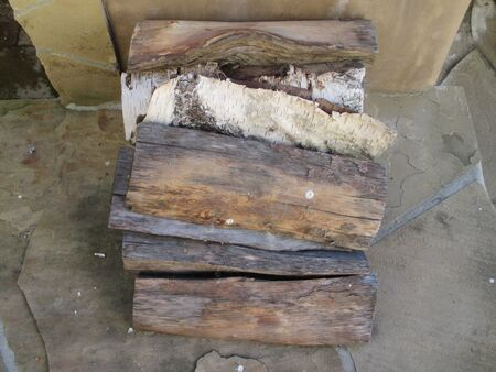 Weathered firewood on an outdoor fireplace