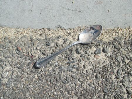 residential street: A dirty metal spoon on a residential street