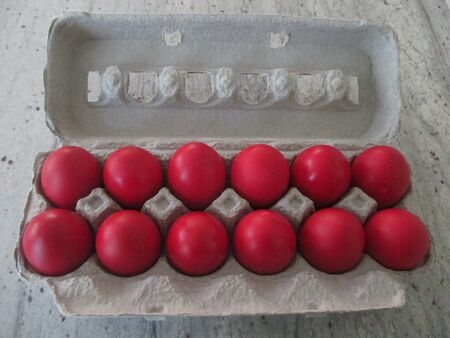 Red Orthodox Easter eggs in an egg carton,